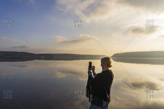 Mid adult woman holding cell phone in front of Lake Aspen in Lerum,  Sweden
