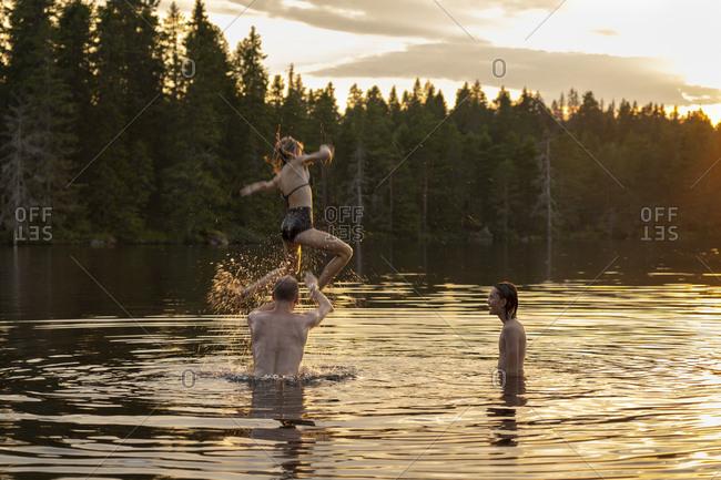 Man throwing teenage girl over lake at sunset