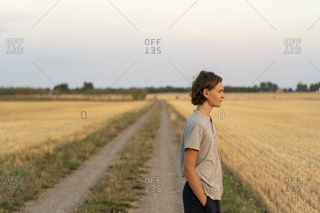 Teenage boy standing on rural road