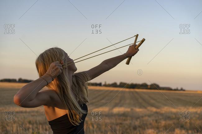 Teenage girl using sling shot in field