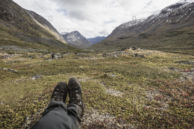 Boots of man sitting on plateau in Norrbotten,  Sweden