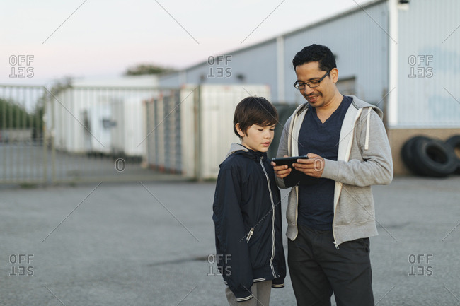 Father and son using smart phone