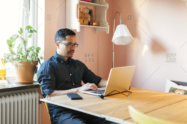 Man using laptop at dining table