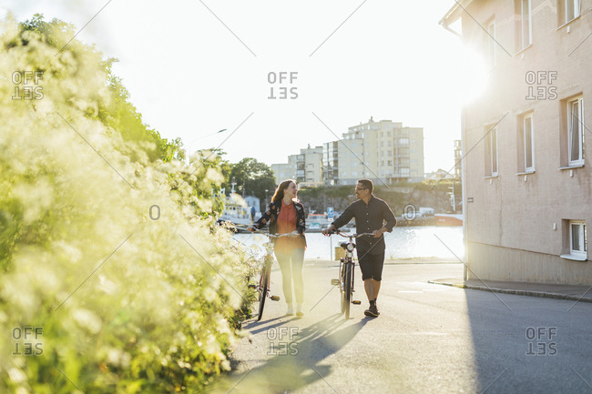 Couple with bicycles on suburban street