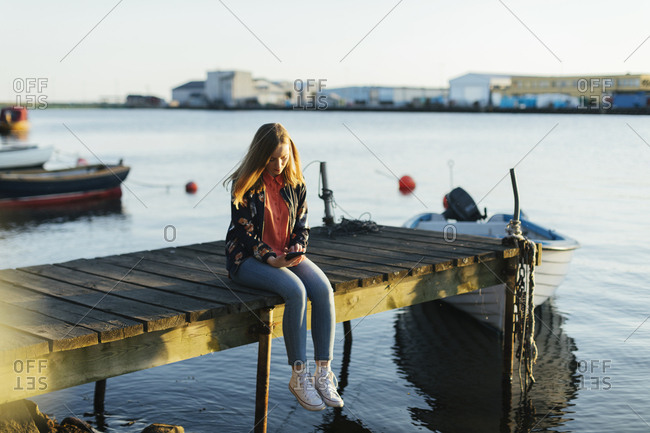 Woman sitting on jetty using smart phone