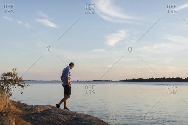 Man walking on rock by sea