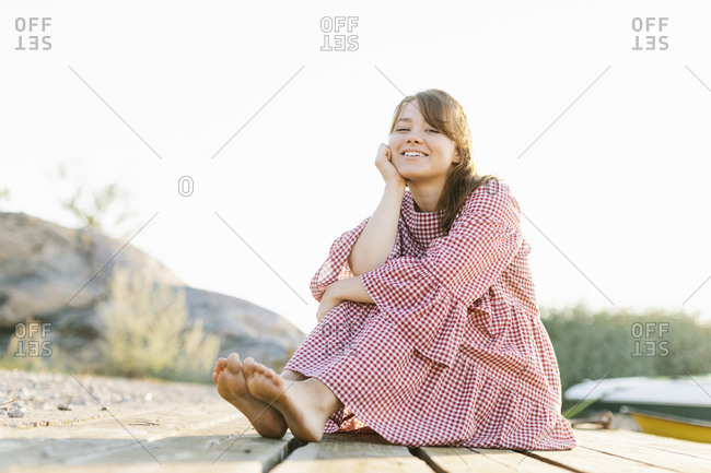 Young woman wearing checked dress hugging her knees
