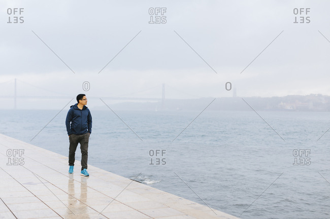 Man walking by Tagus river in Portugal