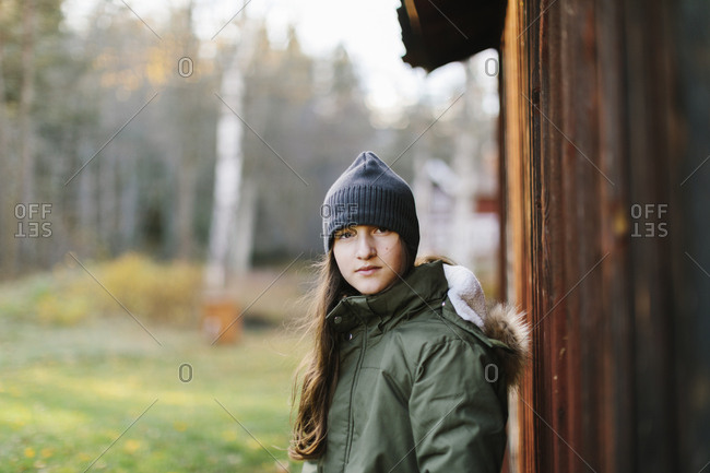 Girl wearing beanie by wooden wall