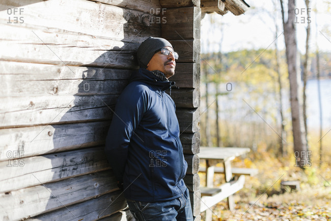 Man wearing beanie and jacket leaning on log cabin