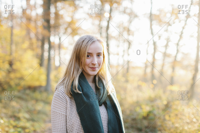Young woman wearing green scarf in forest