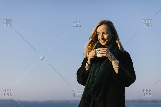 Young woman holding mug against clear sky