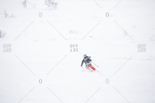 Woman skiing down snowy mountain
