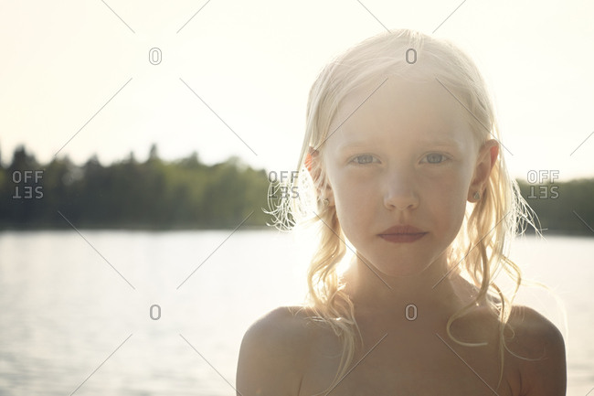 Girl back lit by sunbeam in front of a lake
