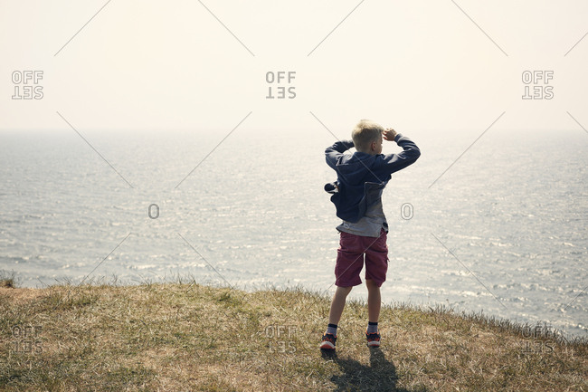 Boy shielding eyes on hill above sea