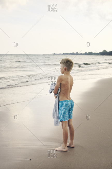 Boy carrying towel on beach