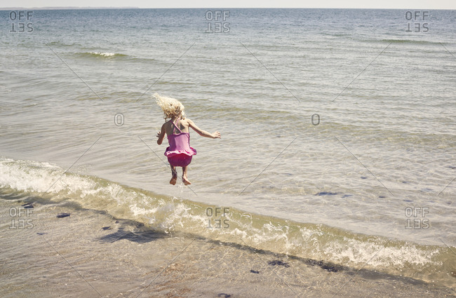 Girl jumping in wave on beach
