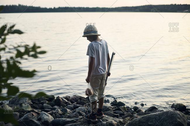 Boy holding fishing rod by lake