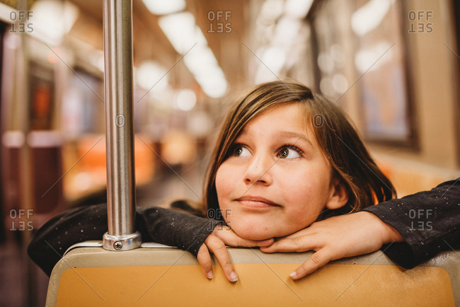 Little girl eagerly rides the subway to her destination