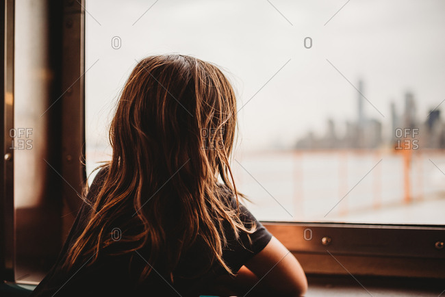 Little girl on ferry looks at the NYC skyline from the window