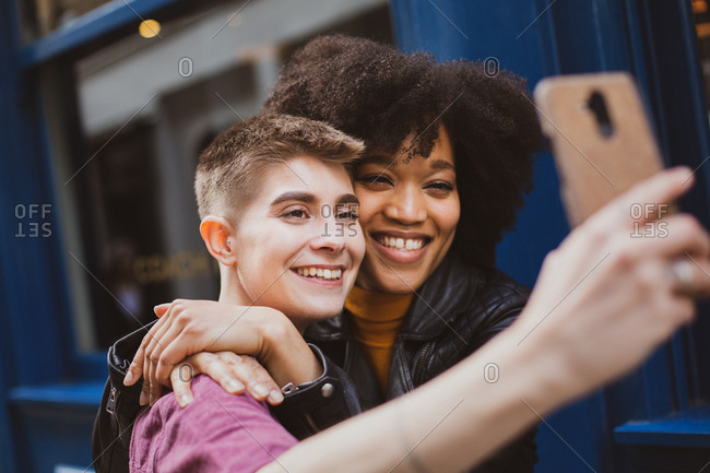Young adult lesbian couple taking selfie in London