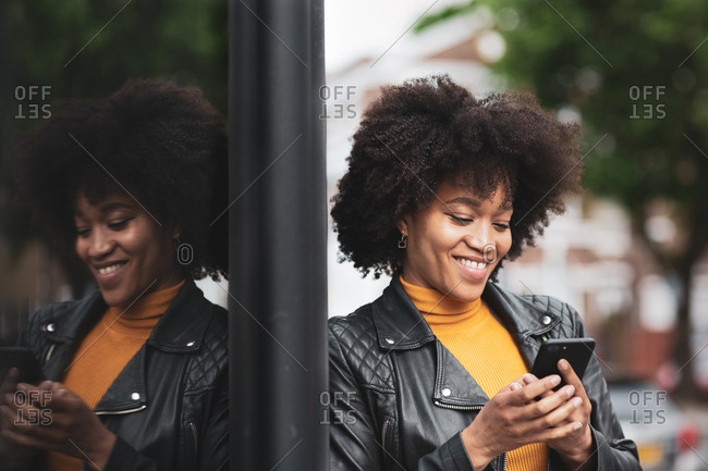 African American young adult female using smartphone in city
