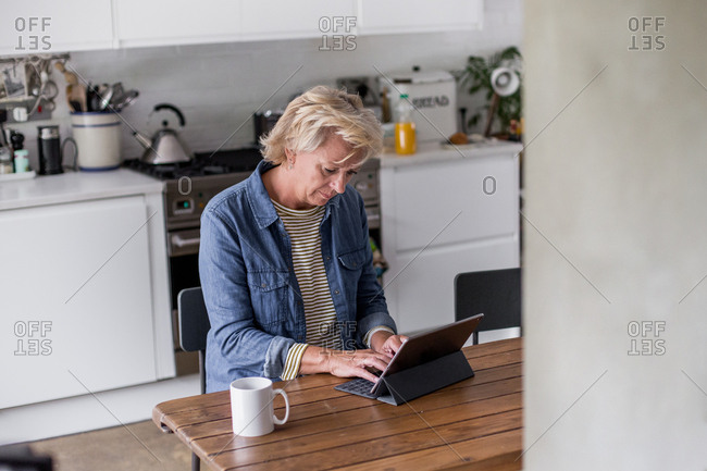 Mature adult woman in kitchen using a digital tablet with keypad
