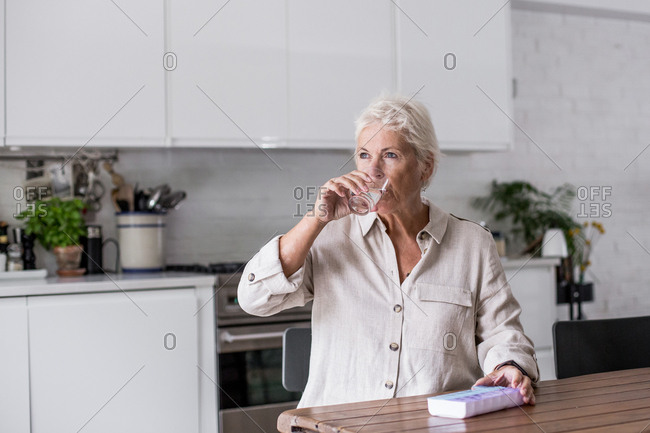 Mature adult woman taking medicine at home in the kitchen