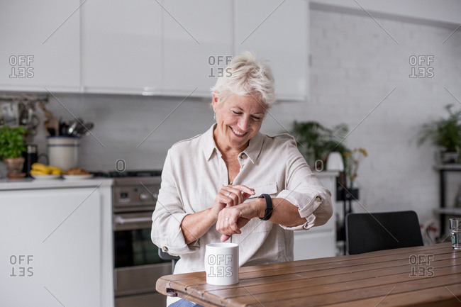 Mature adult woman looking at smartwatch smiling