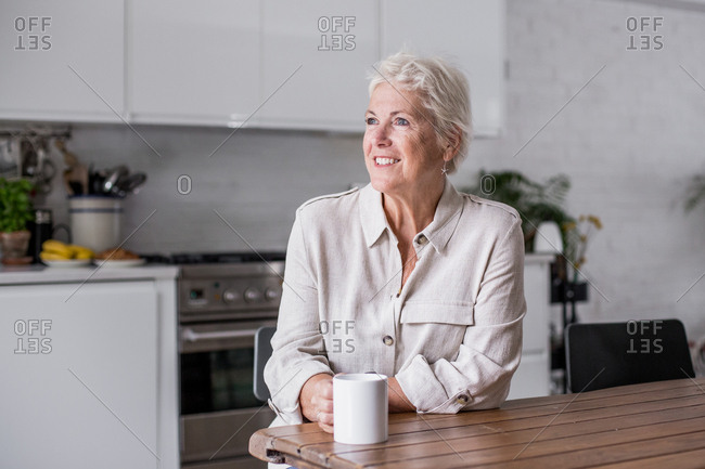 Mature adult woman looking out of window with a mug of tea