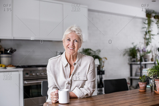 Portrait mature adult woman looking out of window with a mug of tea