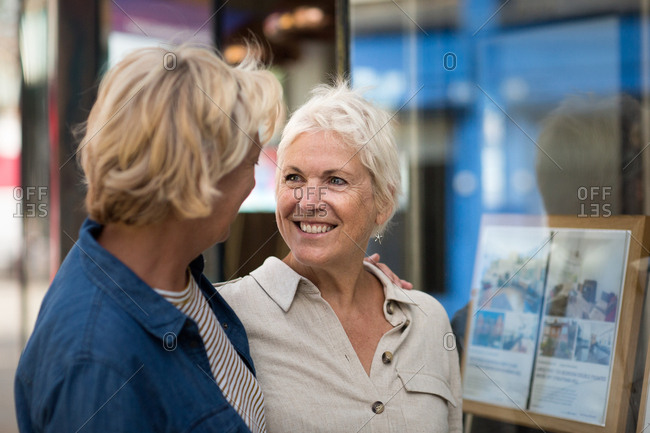 Mature lesbian couple looking at real estate agency window