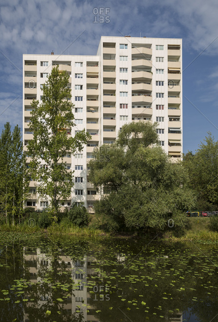 A tower block is reflected in a lily pond at a park in Berlin, Germany