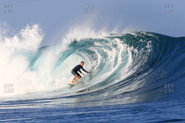 A surfer rides a large crashing wave in Indonesia