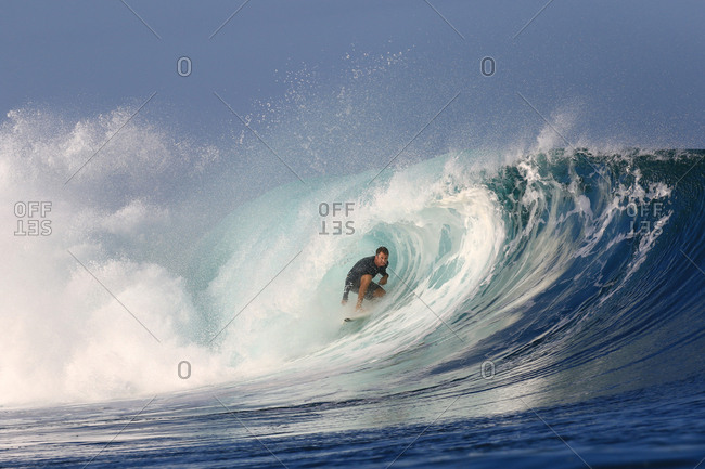 Male surfer rides inside a large wave in Indonesia