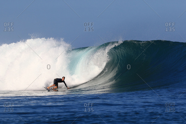A surfer rides the end of a large wave in Indonesia