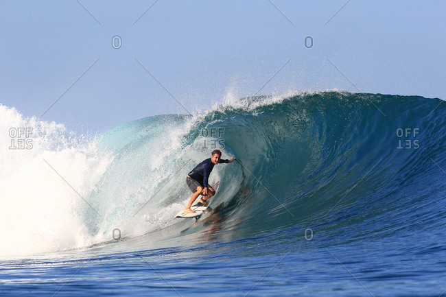 A surfer rides under the curl of a large wave in Indonesia