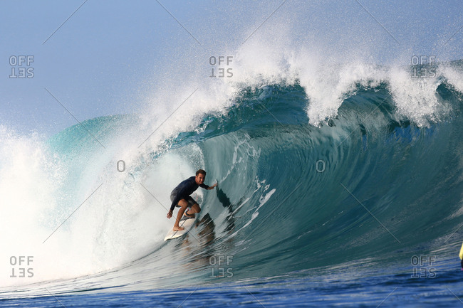 Male surfer inside a large wave in Indonesia