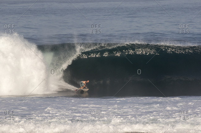 A surfer rides a large wave in Indonesia