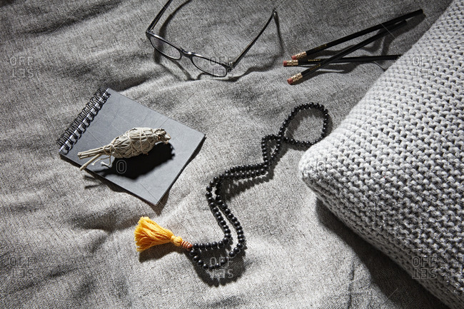 Sage on notebook beside glasses, pencil and prayer beads