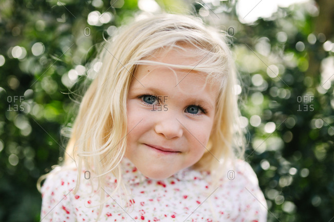 Close up portrait of a sweet little blonde girl with blue eyes outdoors