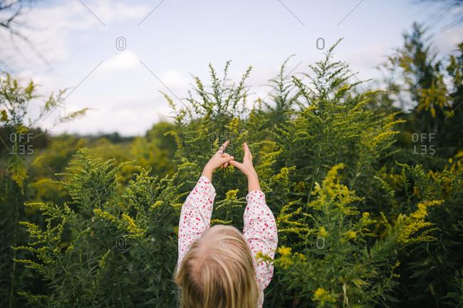 Blonde girl reaching up at yellow wildflowers