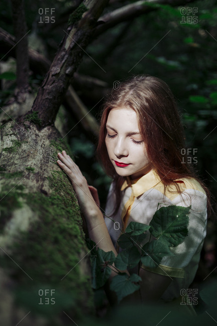 woman stands near a tree with her hand on a tree trunk