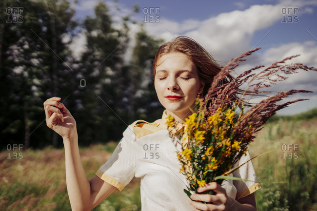 A woman walks in the open air with a bouquet of flowers in the field