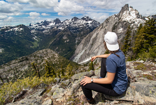 Young hiker girl gazes at distant mountains in Alpine Lakes Wilderness