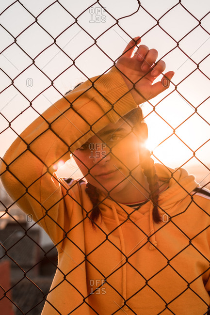 Young woman behind bars on a sunset