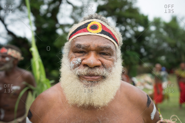 Kokopo, East New Britain, Papua New Guinea - July 11, 2019: Papuan man with white hair and beard poses in traditional attire
