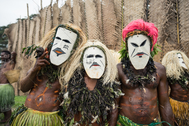 Men wearing white masks with painted faces after performing a dance