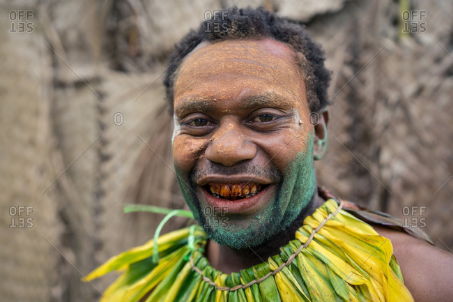 Kokopo, East New Britain, Papua New Guinea - July 11, 2019: Papuan man smiles for a portrait with his painted face and red teeth