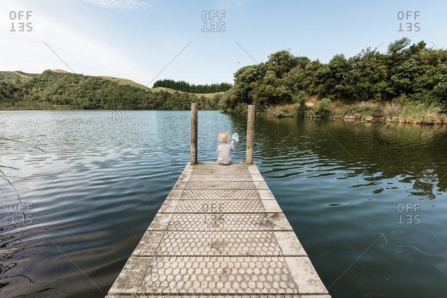 Toddler boy sitting on a wooden dock at a lake
